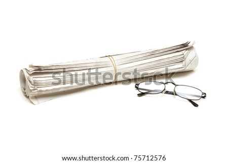 A rolled newspaper and a pair of reading glasses isolated on white.