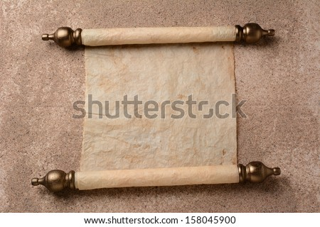 A rolled out scroll of parchment on a sand covered floor. The paper is blank ready for your copy.