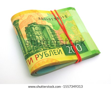 A rolled up bundle of Russian banknotes of 200 rubles lies on a white background. Not isolated. Denominations are connected by elastic band. News of microcredit organizations about loans and deposits #1557349313
