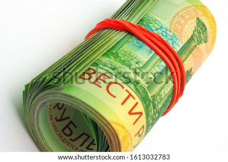 A rolled up bundle of Russian banknotes of 200 rubles lies on a white paper background. Denominations are connected by an elastic band. News of microcredit organizations about loans and deposits