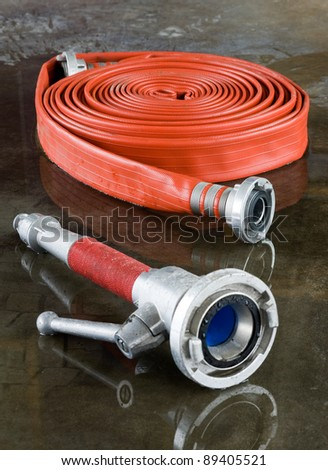 A rolled up firehose and a nozzle on the wet floor in a fire station used by firefighters - stock photo