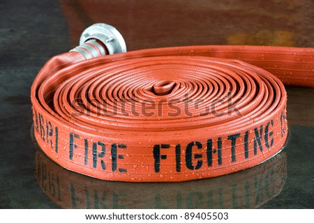 A rolled up firehose on the wet floor in a fire station used by firefighters