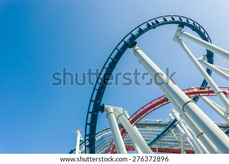 a roller coaster's loop with blue sky