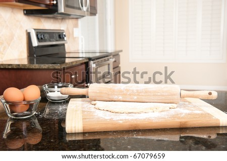 A rolling pin and dough in the forefront of a modern domestic kitchen.