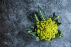 A romanesco cabbage placed in the right of a dark surface with negative space