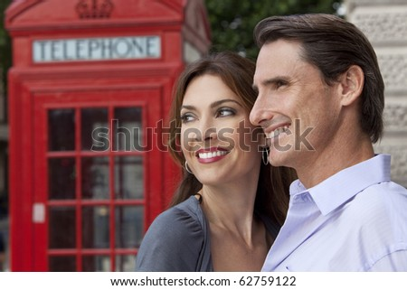 A romantic happy man and woman couple in London, England, with a classic red telephone box out of focus behind him - stock photo