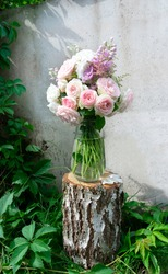 A romantic photo with a bouquet of delicate pink English roses standing in a vase on a birch tree stump. Romantic bouquet on the background of a concrete wall entwined with virginia creeper.