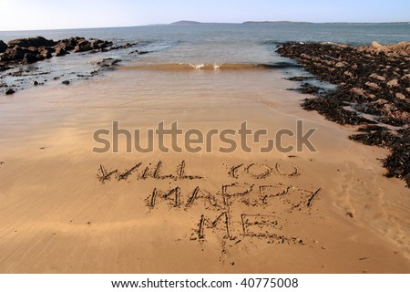 a romantic proposal of will you marry me inscribed on the beach with waves in the background on a hot sunny day