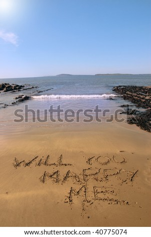 a romantic proposal of will you marry me inscribed on the beach with waves in the background on a hot sunny day - stock photo