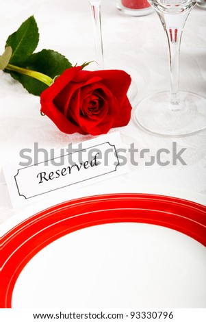 A romantic red and white place setting shows a reserved table at an elegant restaurant ready to celebrate an anniversary or Valentine's Day.