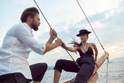 a romantic trip by sea on the yacht of a stylish couple in love, who emotionally show their feelingshe is wearing a white linen shirt and pants, she is wearing a black top, pants and a hat