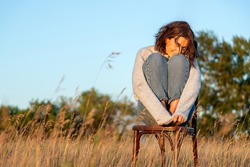 A romantic walk of a curly-haired woman in a  jeans and knitting sweater sitting on old retro chair against the background of the a field. The concept of female freedom, emancipation and love