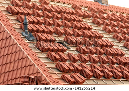 A roof under construction with stacks of roof tiles ready to fasten #141255214