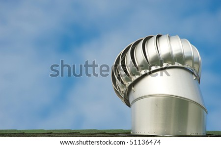 A roof ventilator in motion against a brilliant blue sky with room for text. - stock photo