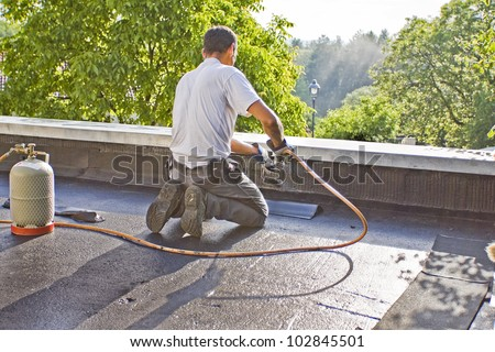 A Roofer With A Gas Burner Is Kneeling On A Roof And