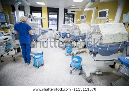 A room in a post delivery room of a hospital full of medical equipment and incubators. Treating children who have been born prematurely.