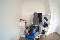 A room littered with clothes waiting for the closet to be installed