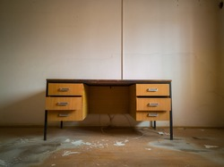 A room with office equipment in an abandoned factory. An old dirty and dusty office with an open drawer desk and cobwebs around the corners. Cracked and peeled lime on the walls. - Image