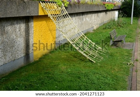 a rope net is attached to the concrete wall and is obliquely fixed to the ground. children can play sailors and test stability like spiders. hanging diagonally down Foto stock ©