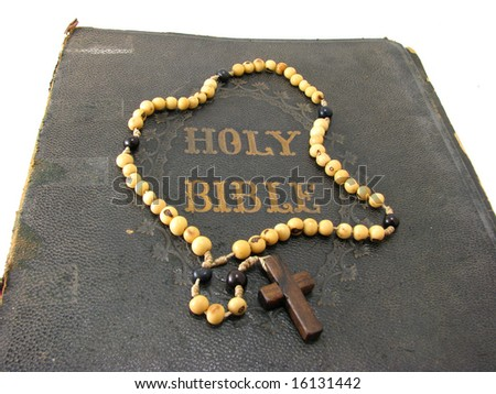 A rosary laying on a worn antique Bible.