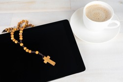 A rosary on the black screen of a tablet computer, beside a cup of coffee