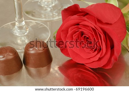 A rose, two chocolate pralines and two champagne glasses on a tray of brushed metal.