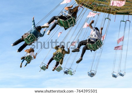 A rotating chair swing ride carousel with teenagers enjoying the ride in a parisian amusement park. #764395501