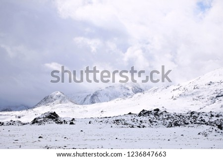 a rough mix of cold, ice, snow in the expanses of the Icelandic mountains. Picture of the sun coming out after a snow blizzard in the mountains