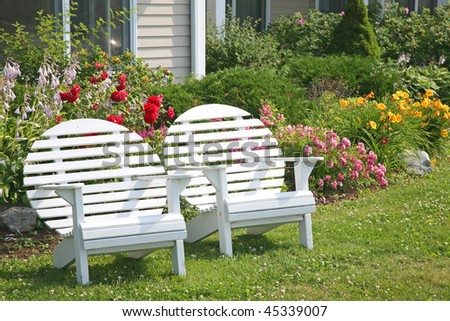 A round back Adirondack chair fondly know as a moon chair in front of a home and flower beds.