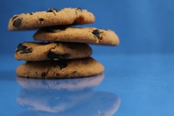 a round cookie with chocolate drops is stacked on top of each other on a blue bright saturated background with a reflection side view of copy space