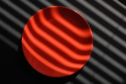 A round flat coral-red ceramic plate on a black plastic background is illuminated by sunlight through the blinds. Hard light draws clear stripes and creates an abstraction.
