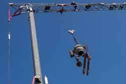 A round grey concrete mixer and a red movable carriage trolley are suspended from the boom hook of a tower crane with a grey vertical column and a red counterweight