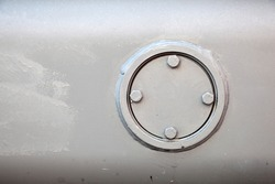 a round hole in the gray tank, closed with a round lid on four screws