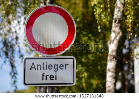 A round red white road sign in Germany. For motor vehicles, cars and trucks the entrance is prohibited. A green tree with soft bokeh in the background except for residents. #1527131348