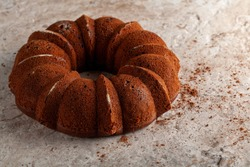 A round sponge cake fresh out of oven with crumbles and cacao powders cooling on top of a marble or stone kitchen countertop. The impression of the cake mold is seen on the rugged appearance of it.