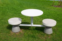 A round table and two high chairs made on a single metal structure of gray color against the background of bright young greenery on a clear sunny day. Recreation park architecture.