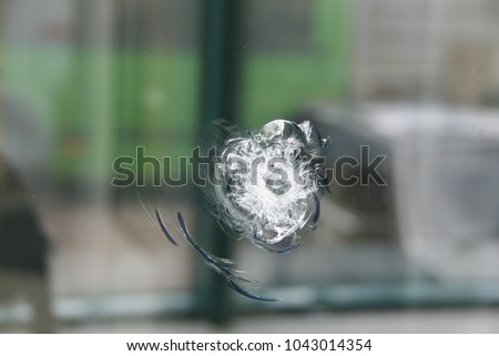 Photo of  A round trace of bullets coming into the thick window glass. The bullet-resistant glass (ballistic glass or transparent armor).