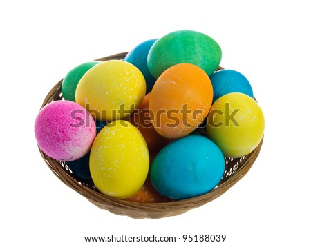 A round wicker basket full of dyed Easter eggs