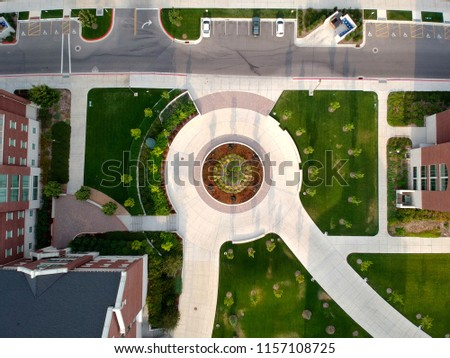 A roundabout with vegetation and structures. #1157108725