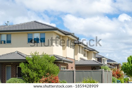 A row of Australian modern suburban townhouses in Melbourne's residential neighbourhood. Townhouses in Australia are connected to one another in a row and are usually two or three stories tall.
