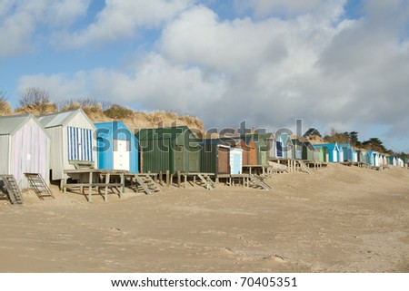 A row of beachhuts, multicoloured, with steps and boardwalks on a beach backed by a sand dune, blue sky and clouds.
