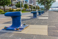 A row of blue marine bollards are used as decoration on the boardwalk at Yarra's Edge in Melbourne, Australia