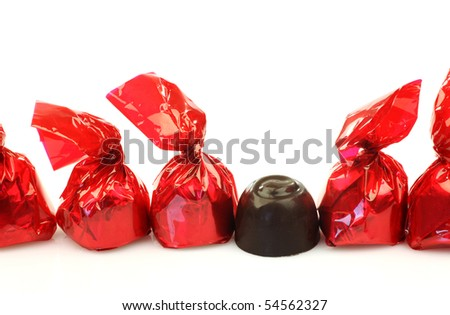 a row of bonbons wrapped in red shiny paper and one unwrapped ready to eat on a white background