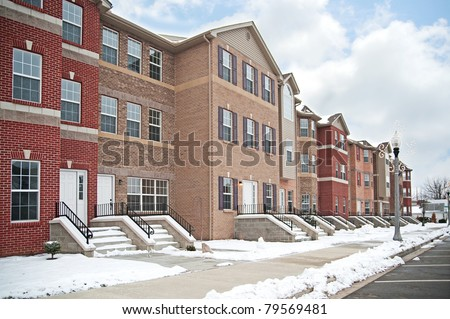 A row of brick apartment condominiums in winter with snow on the steps and curb.