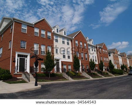 A row of brick condos or townhouses beside a street.