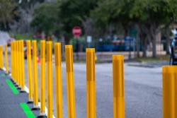 A row of bright yellow metal sticks or pylons used as barricades at a road construction barrier site. The closed road signs protect the sidewalk as traffic control during roadwork.