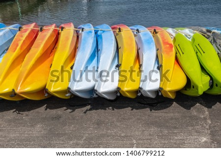A row of brightly coloured kayaks sitting on the ground, colours included yellow green and blue #1406799212