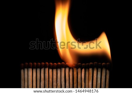 A row of burning matches on a black background. The flame moves from the match to the match