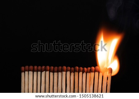 A row of burning matches on a black background. The flame moves from the match to the match. Fire is inevitable