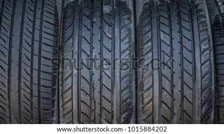 A row of car tires, wet with dew, on display